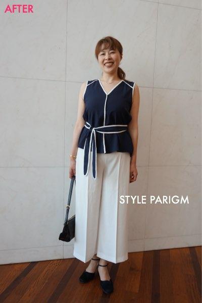 紺色のブラウスと白のワイドパンツのコーディネートで笑顔の女性
